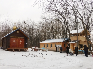 Memorial shrine (left) and wooden church in which an Orthodox service was underway